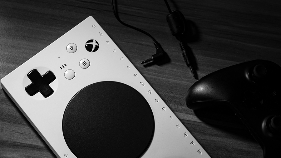 A close-up of the Xbox Adaptive Controller with 2 mono audio cables and an Xbox controller